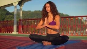 Female meditates outdoors. Caucasian woman sitting in lotus position on the bridge stock footage