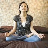 Female meditating. Asian female sitting on bed meditating Stock Photo