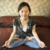 Female meditating. Asian female sitting on bed meditating Stock Photos