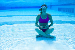 Female meditating underwater. Female meditating in yoga pose with eyes closed underwater in swimming pool Royalty Free Stock Photos