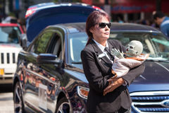 Female Men In Black Agent Carries Alien Baby In Parade Stock Image