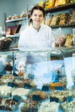 Female merchant is pouring on nuts into bag. In the shop Stock Photo
