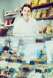 Female merchant is pouring on nuts into bag. In the shop Royalty Free Stock Photos