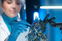 Free Female Microelectronics Engineer Works In A Scientific Laboratory On Computing Systems And Microprocessors. Professional Royalty Free Stock Photo - 215949085