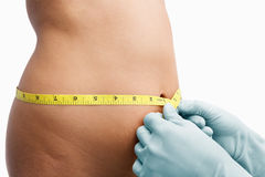 Female mid section being measure. By doctor hand before liposuction over white background Royalty Free Stock Photo