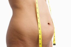 Female mid section with measuring tape. For obesity issue Royalty Free Stock Images