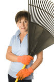 Female middle age senior gardener leaf rake Royalty Free Stock Image