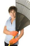 Female middle age senior gardener leaf rake royalty free stock image