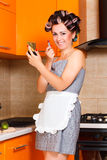 Female middle-aged housewife paints her lips in the kitchen. Middle-age woman with apron paints her lips in the kitchen Stock Image