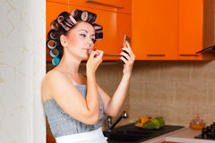 Female middle-aged housewife paints her lips in the kitchen. Middle-age woman with apron paints her lips in the kitchen Royalty Free Stock Image