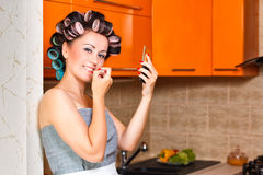 Female middle-aged housewife paints her lips in the kitchen. Middle-age woman with apron paints her lips in the kitchen Stock Photography