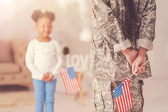 Female in military uniform holding American flag. American patriots. The focus being on a female figure standing in front of a cute little girl holding an royalty free stock photography