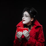 Female mime holding heart. Funny female mime holding red heart on black background royalty free stock photo