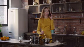 Female mixing up dinner and speaking on cell. stock footage