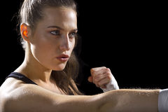 Female MMA Fighter. Punching.  black background Stock Photos