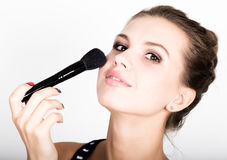 Female model applying makeup on her face. Beautiful young woman applying foundation on her face with a make up brush. Stock Photos