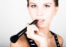 Female model applying makeup on her face. Beautiful young woman applying foundation on her face with a make up brush. Royalty Free Stock Photo