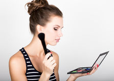 Female model applying makeup on her face. Beautiful young woman applying foundation on her face with a make up brush. Stock Photography