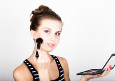 Female model applying makeup on her face. Beautiful young woman applying foundation on her face with a make up brush. Royalty Free Stock Photography