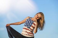 Female model on the background of sky in a t-shirt with the Amer Royalty Free Stock Photo