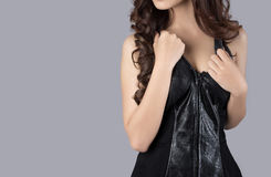 Female model body wearing a leather dress. In studio Stock Photography