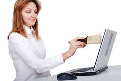 Female model is brushing/cleaning her laptop with. Brush Royalty Free Stock Image