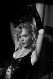 Female model with curly blond hair wearing black leather bodysuit with laces and long leather gloves in black and white photo Royalty Free Stock Photo