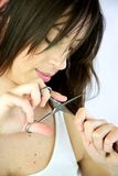 Female model cuts her own hair. Female model cuts her own long hair Royalty Free Stock Image