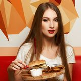 Female model demonstrating burger lying on round wooden plate. Portrait of beautiful young woman holding round tray with delicious burger, salad and fried potato Stock Image