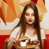 Female model demonstrating burger lying on round wooden plate. Portrait of beautiful young woman holding round tray with delicious burger, salad and fried potato Stock Photography