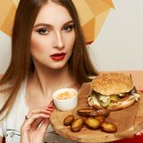 Female model demonstrating burger lying on round wooden plate. Portrait of beautiful young woman holding round tray with delicious burger, salad and fried potato Stock Images
