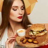 Female model demonstrating burger lying on round wooden plate. Portrait of beautiful young woman holding round tray with delicious burger, salad and fried potato Stock Photos