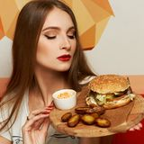 Female model demonstrating burger lying on round wooden plate. Portrait of beautiful young woman holding round tray with delicious burger, salad and fried potato Royalty Free Stock Images