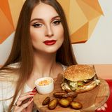 Female model demonstrating burger lying on round wooden plate. Portrait of beautiful young woman holding round tray with delicious burger, salad and fried potato Stock Photo