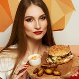 Female model demonstrating burger lying on round wooden plate. Portrait of beautiful young woman holding round tray with delicious burger, salad and fried potato Royalty Free Stock Photo