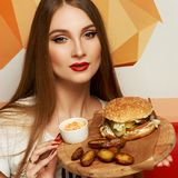 Female model demonstrating burger lying on round wooden plate. Portrait of beautiful young woman holding round tray with delicious burger, salad and fried potato Royalty Free Stock Photos