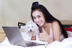 Female model with dog and notebook on bed Royalty Free Stock Photography