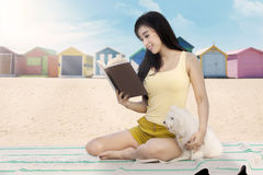 Female model with dog reads book at beach Stock Photo