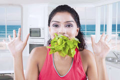 Female model eating spinach in kitchen Stock Photo