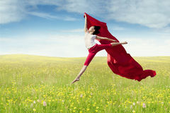 Female model with fabric jumps at field Stock Photography
