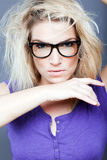Female model with fierce look. Female model with messy hair and fierce look wearing thick eyeglasses royalty free stock photo