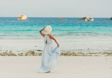 Female model girl in dress and hat posing at tropical beach royalty free stock photos