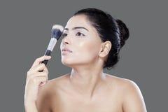 Female model holding makeup brushes Stock Images