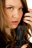 Female model holding pistol close up serious expression Royalty Free Stock Image