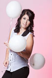 Female model holding three balloons. Caucasian teenage female posing in a white blouse and black jeans with a pink background holding three balloons Stock Photography