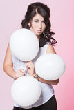 Female model holding three balloons. Caucasian teenage female posing in a white blouse and black jeans with a pink background holding three balloons Royalty Free Stock Photos