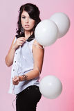 Female model holding three balloons. Caucasian teenage female posing in a white blouse and black jeans with a pink background holding three balloons Royalty Free Stock Photography
