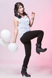 Female model holding three balloons. Caucasian teenage female posing in a white blouse and black jeans with a pink background holding three balloons kicking in Royalty Free Stock Photography