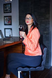 Female model holding wineglass full of red wine. Royalty Free Stock Photo