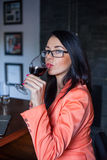 Female model holding wineglass full of red wine. Stock Image